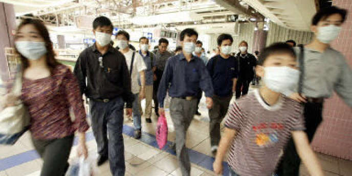 Des personnes portant des masques pour se protéger du syndrome respiratoire aigu sévère (SRAS) à Hongkong, le 22 avril 2003.