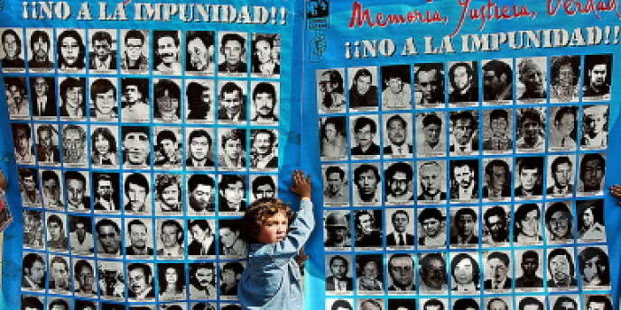 Un enfant devant des photos de victimes du plan Condor au Chili