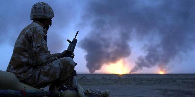 Un soldat britannique observant un puits de pétrole en feu dans le sud de l'Irak, le 20 mars 2003.