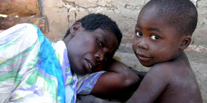 Une femme de 36 ans atteinte du sida, abandonnée par son mari à Kitwe, dans la province de Copperbelt, en Zambie, se repose à l'extérieur de sa maison au côté de son enfant.