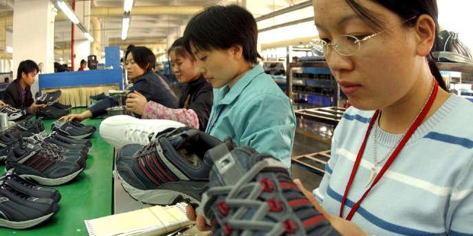 Des ouvrières chinoises confectionnent des chaussures dans une usine de la province du Fujian,le 26 décembre 2004.