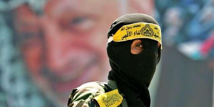 Un membre des Brigades des martyrs d'Al-Alqsa devant un portrait de Yasser Arafat.