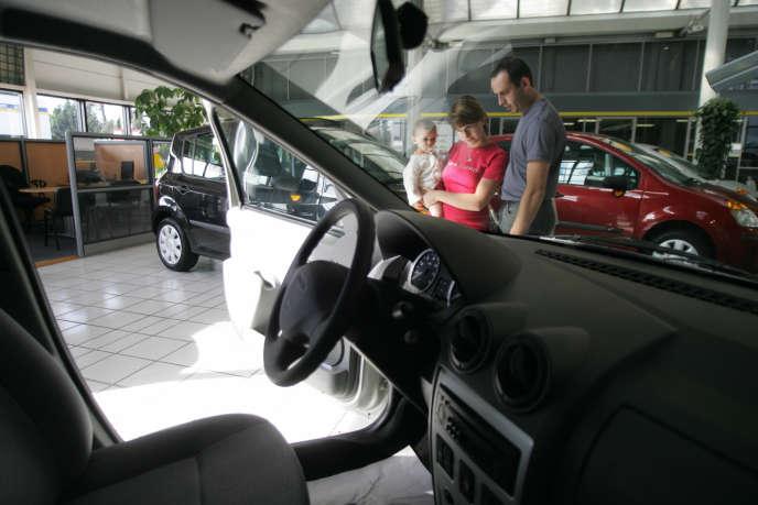 Un couple et leur enfant regarde une Logan chez un concessionnaire de Montpellier, le 9 juin 2005.