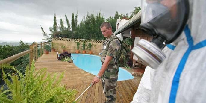 Un soldat français à la Réunion désinfecte une plantation pour lutter contre le chikungunya. Sur le terrain, la « lutte anti-vectorielle » bat son plein, autrement dit la traque de toute eau stagnante pouvant abriter des larves de l'Aedes aegypti.