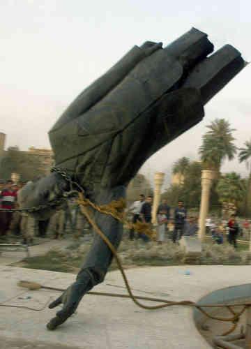 Les Américains prennent Bagdad  le 9 avril 2003 et commencent à renverser ou détruire les symboles de l'ancien régime. Ici, la statue du raïs au jardin d'Al-Fardous de Bagdad est détruite par les marines américains sous le regard curieux de civils irakiens.