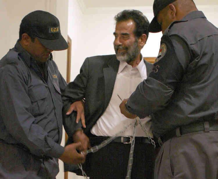 Les gardiens irakiens retirent les menottes de Saddam Hussein, lors de sa première audition, le 1er juillet 2004.
