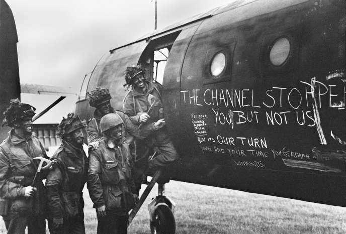 Des soldats britanniques devant leur avion recouvert de slogans, en juin 1944.