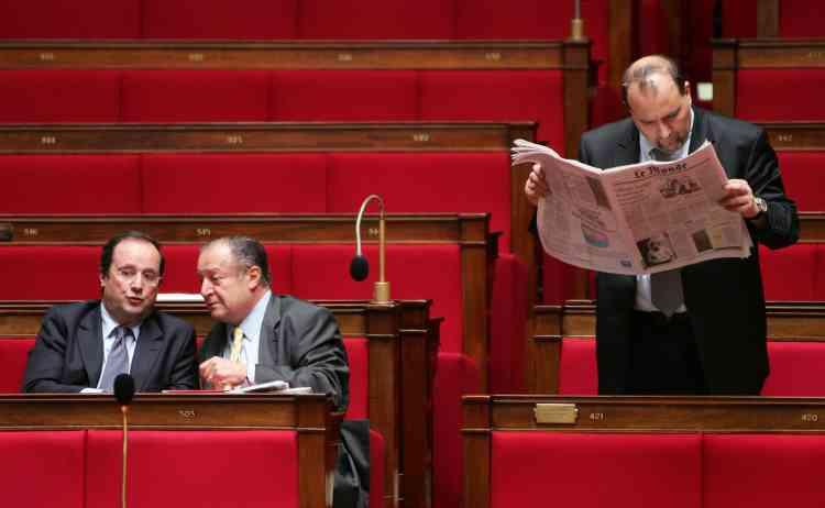 """François Hollande parle avec le député socialiste Tony Dreyfus tandis que Julien Dray lit """"Le Monde"""", à l'Assemblée nationale, à Paris."""