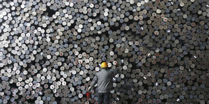 Un travailleur marque des barres de fer dans une usine, en Chine.