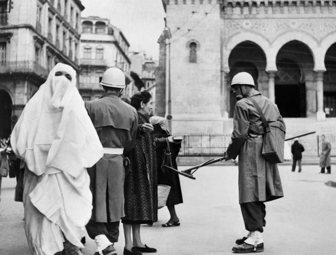 Un soldat français utilise un détecteur de mines sur les passants à Alger le 16 janvier 1957, pendant la guerre d'Algérie, dans le cadre d'une opération de fouille systématique de la partie basse de la Casbah pendant la bataille d'Alger.