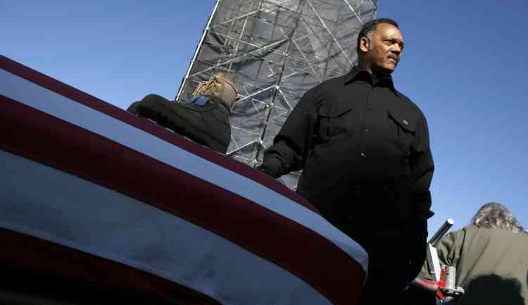 Le révérend Jesse Jackson, militant des droits civiques et opposant à la guerre devant une paire de rangers posées sur un cercueil recouvert du drapeau des Etats-Unis.