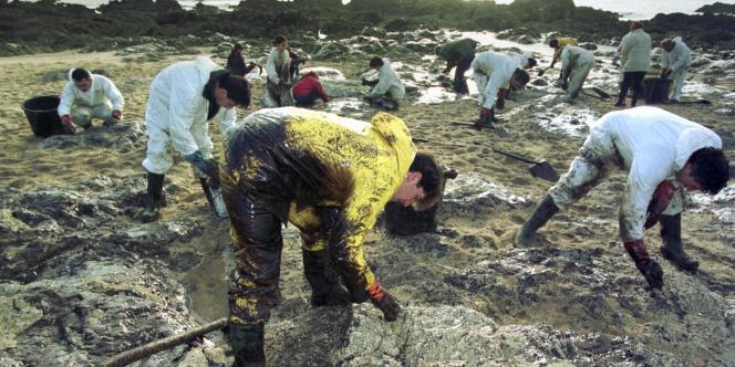 Des bénévoles nettoient à la main les rochers d'une crique de la Côte sauvage du Croisic, le 29 décembre 1999, à la suite du naufrage de l'