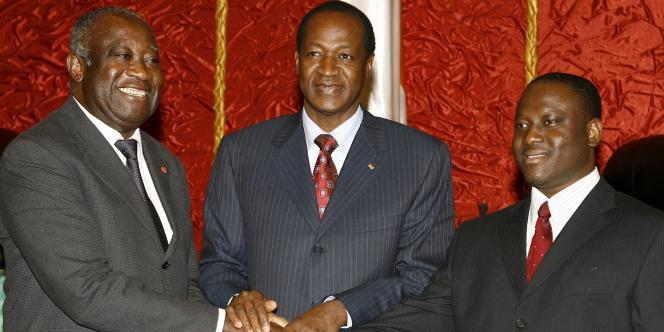Le président ivoirien Laurent Gbagbo (gauche) et le chef des Forces nouvelles Guillaume Soro (droite) se serrent la main, le 4 mars 2007, après avoir signé un accord pour relancer le processus de paix en Côte d'Ivoire, en présence du président burkinabé Blaise Compaoré.