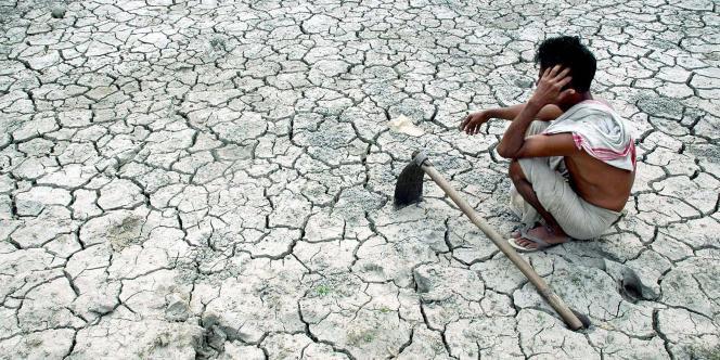 Un fermier attend la pluie près d'Assam, en Inde, en août 2006. Le réchauffement entraîne de graves pénuries d'eau dans les pays en développement.
