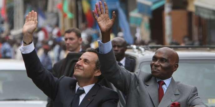 Nicolas Sarkozy salue la foule aux côtés du président sénégalais Abdoulaye Wade, jeudi 26 juillet, à Dakar.