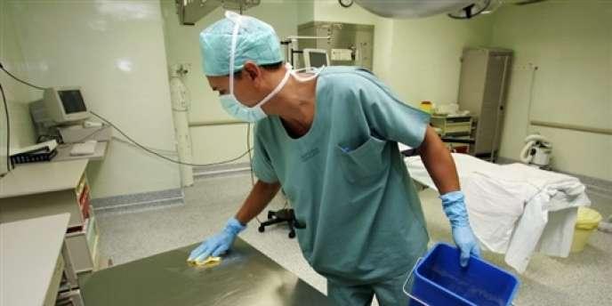Un agent d'entretien désinfecte une table d'intervention dans le bloc opératoire de l'hôpital Nord, le 24 août 2005 à Marseille.