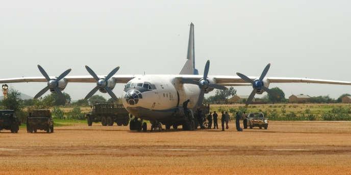 Des soldats de l'armée soudanaise déchargent le contenu des soutes d'un appareil Antonov pour le mettre dans des camions militaires, sur l'aire militaire de l'aéroport d'El Geneina.