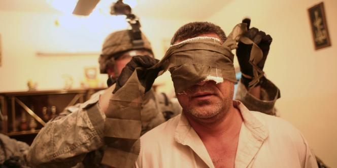 Un soldat américain arrêtent un Irakien lors d'une opération de nuit dans le sud-est de Bagdad.