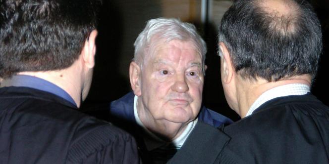 Emile Louis s'entretient avec ses avocats, dans le box de la cour d'assises du Var à Draguignan, à l'ouverture du procès des disparues de l'Yonne, en mars 2004.