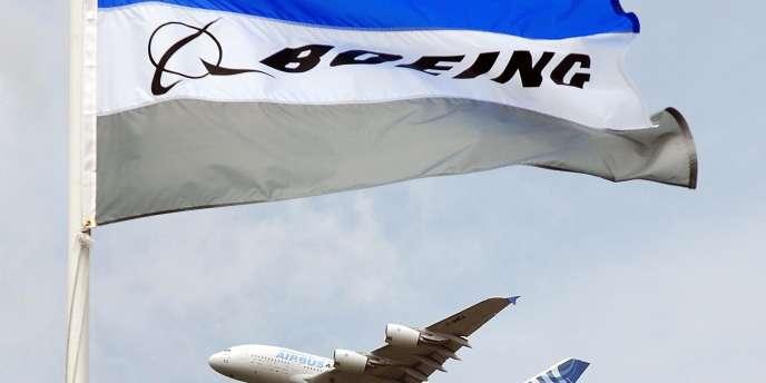 Un Airbus A380 passant près d'un drapeau du constructeur américain Boeing.