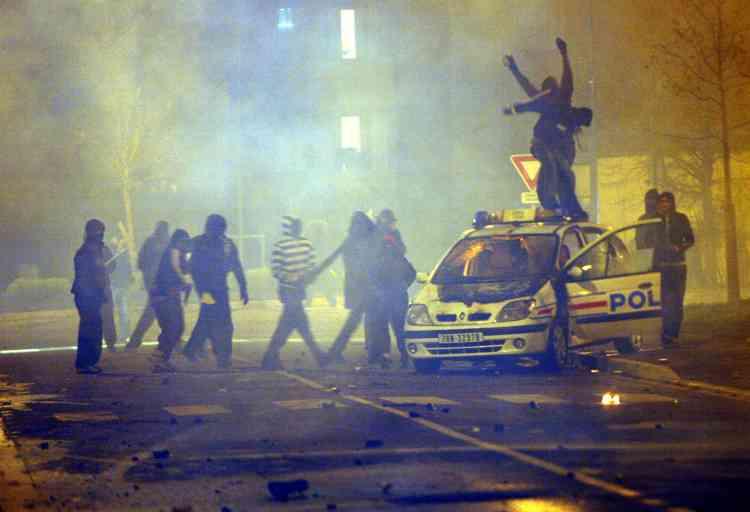 Des jeunes vandalisent une voiture de police à Villiers-le-Bel, lundi soir 26 novembre.