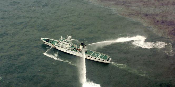 En Corée du Sud, un navire des gardes-côtes essaye de disperser une marée noire, en décembre 2007.