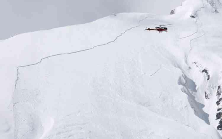 Un hélicoptère survole une palque de glace avant de déclencher artificiellement une avalanche dans la vallée de la Sionne à Anzere. Trois skieurs sont morts, ce week end, dans des avalanches du massif alpin.