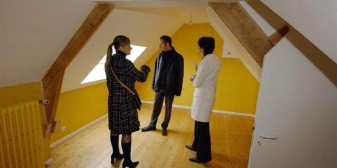 Une négociatrice immobilière fait visiter une maison à un couple à la recherche d'un logement.
