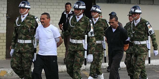 Gerardo Aguilar, alias Cesar (à gauche), et Enrique Rojas, les deux membres des FARC faits prisonniers lors de l'opération de libération des otages, arrivent sur une base militaire à Bogota, en juillet 2008.