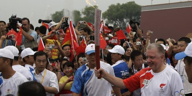 Hein Verbruggen, portant la flamme olympique, à Pékin, le 6 août 2008.