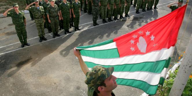Des soldats saluent le drapeau de l'Abkhazie — république dont l'indépendance autoproclamée est reconnue par la Russie depuis 2008 —, le 16 août, à Soukhoumi, la capitale.
