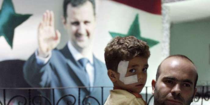 Un homme et son fils devant une affiche à l'effigie de Bachar Al-Assad, en septembre 2008.