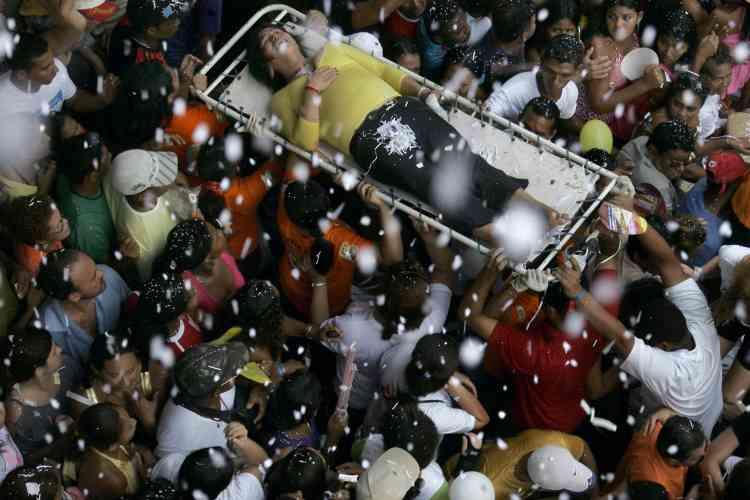 Une femme est évacuée à travers la foule.