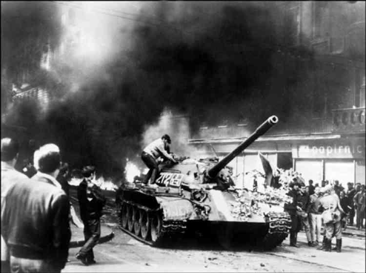 """Un jeune Pragois monte sur un char soviétique T-54 dans la rue de Vinohrady, près de la Maison de la Radio à Prague, le 21 août 1968 pendant des affrontements entre des manifestants et des soldats des forces du Pacte de Varsovie qui ont occupé la Tchécoslovaquie dans la nuit du 20 au 21 août 1968 pour étouffer le réveil réformiste communiste du """"Printemps de Prague""""."""
