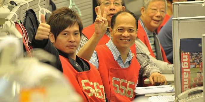 Des traders saluent la hausse de la Bourse de Hongkong.