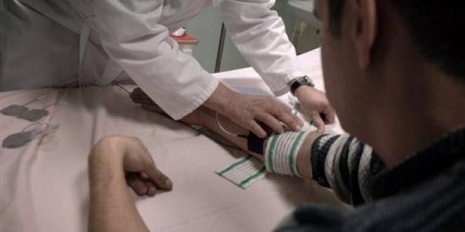 Un médecin psychiatre pose des électrodes sur le bras d'un patient dans un hôpital psychiatrique de Lyon.