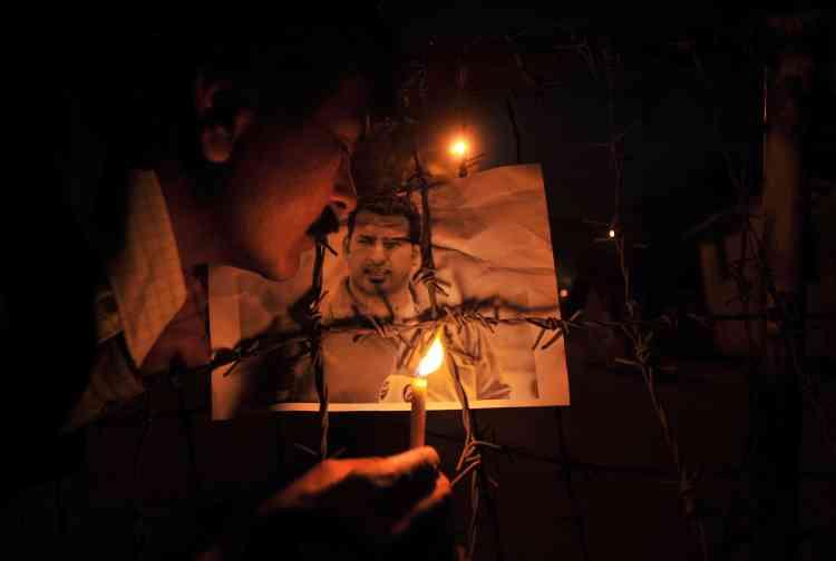 Un journaliste accroche une photo de Muntadar Al-Zeidi sur les barbelés qui entourent le consulat américain à Lahore.