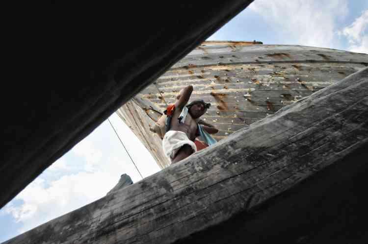 Dans le port de Jakarta, un ouvrier charge des sacs sur un bateau.