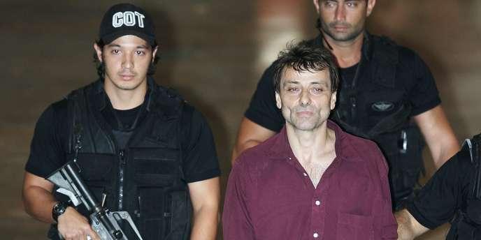 Cesare Battisti lors de son arrivée à l'aéroport de Brasilia, entouré de policiers, le 19 mars 2007.