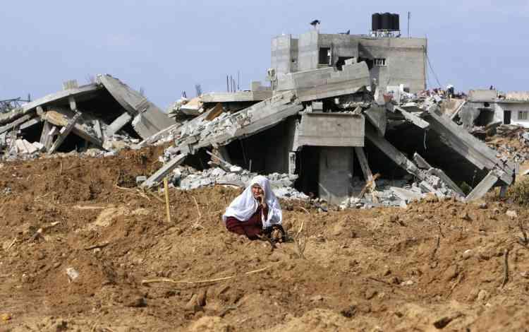 Une femme assise devant des maisons détruites à Djabalia. Selon l'Office central palestinien de statistique, la note totale de la reconstruction s'élévera à près de deux milliards de dollars.