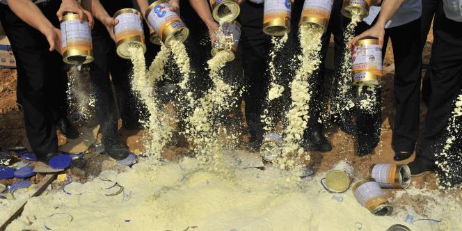 Des agents de l'inspection sanitaire vident des boîtes de lait en poudre contaminé dans une décharge de la province chinoise de Guangdong, le 19 septembre 2008.