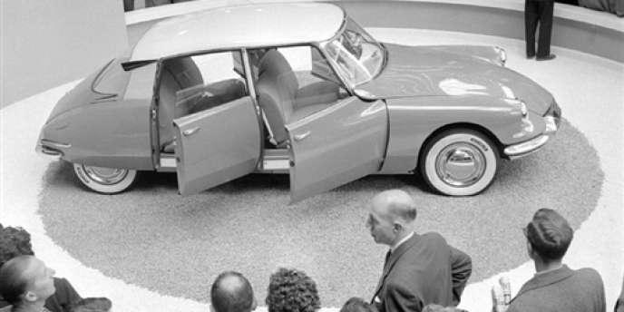 Des visiteurs admirent la DS de Citroën lors du 42e salon de l'automobile, le 7 octobre 1955, au Grand Palais, à Paris.