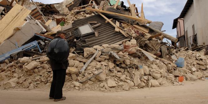 Un homme devant un bâtiment détruit dans le village d'Onna, près de L'Aquila, dans le centre de l'Italie, mercredi 8 avril 2009.