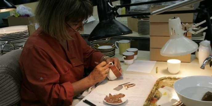 Une employée d'une entreprise de manufacture de porcelaine travaille, le 24 août 2004 à Limoges.