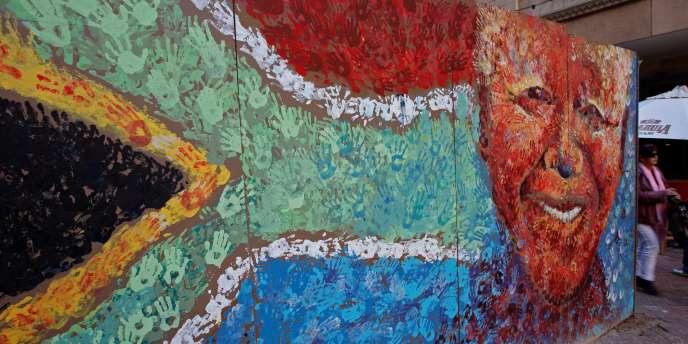 Une fresque murale représentant Nelson Mandela, le premier président noir d'Afrique du Sud, sur le drapeau national.