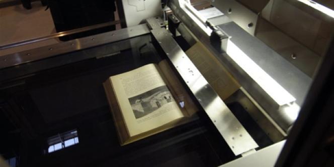 Un livre est en cours de numérisation sur un scanner, le 17 mars 2006 sur un stand du Salon du livre à Paris, avant d'être mis en vente sur la Toile.