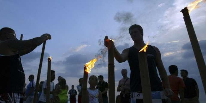 Des touristes allument des torches de bambou sur la plage de Kuta, à Bali, pour rendre hommage aux 202 victimes tuées dans des attentats à la bombe en 2002.
