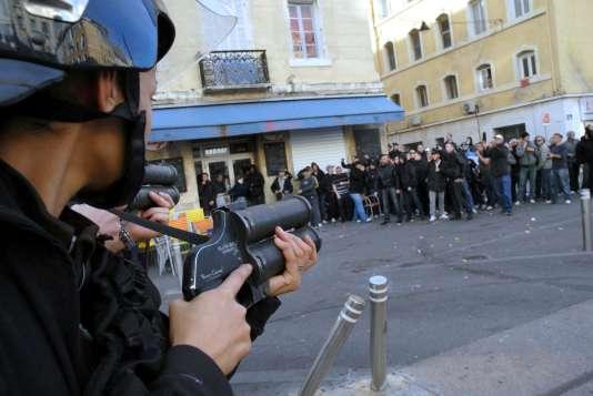 """Un policier, équipé d'un """"flashball"""", s'interpose entre des groupes de supporteurs marseillais et parisiens, dimanche 25 octobre à Marseille."""