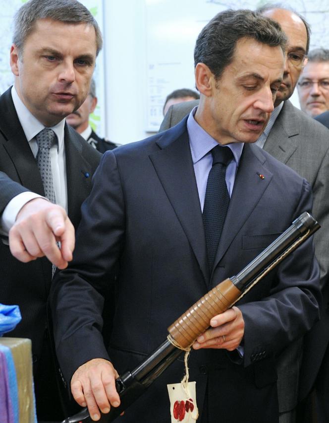 Nicolas Sarkozy examine une arme saisie par la police, le 24 novembre 2009 à Bobigny.