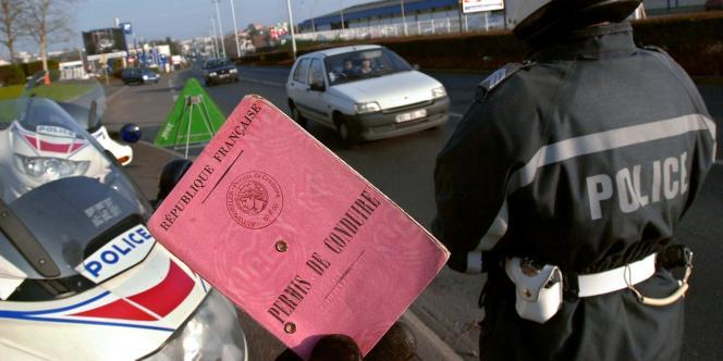 Un policier montre un permis de conduire, le 18 décembre 2002 sur un boulevard de la ville de Caen, lors d'une opération de contrôles de vitesse.